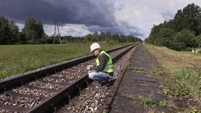 Befördern Sie die Arbeitskraft mit dem Zug, die Tablet-PC verwendet und nahe Eisenbahn geht stock footage