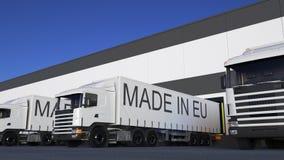 Befördern Sie halb LKWs mit GEMACHT IN EU-Titel auf dem Anhängerladen oder -entleerung Wiedergabe des Straßenfrachttransportes 3D Stockfoto