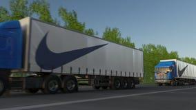 Befördern Sie halb LKWs mit Nike-Aufschrift und -logo, die entlang Waldweg fahren Redaktionelle Wiedergabe 3D Lizenzfreie Stockfotografie