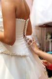Befestigen des Hochzeitskleides stockbild