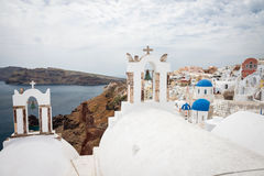 Beffroi avec les dômes bleus des églises, Oia, Santorini Images stock
