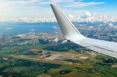Beflügeln Sie Ansicht vom Flugzeugfenster zum Flügel, zum Flughafen, zum Meer, zur Stadt und zu den Wolken Lizenzfreie Stockbilder