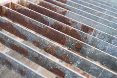 Befleckte Stahlgrillkanaldeckel- oder -abwasserabflussabdeckung, Abschluss herauf Bild Stockbild