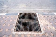 Befleckte Stahlgrillkanaldeckel- oder -abwasserabflussabdeckung, auf allgemeinem Fußweg, Kopienraum auf der Straße Lizenzfreie Stockfotos