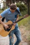 Begåvad gitarrist som spelar skogen som fotvandrar begrepp royaltyfri fotografi