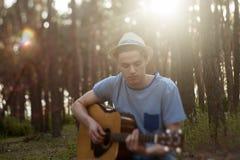 Begåvad gitarrist som spelar skogen som fotvandrar begrepp arkivfoto