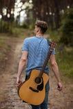 Begåvad gitarrist som spelar skogen som fotvandrar begrepp royaltyfri bild
