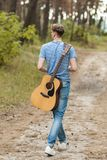 Begåvad gitarrist som spelar skogen som fotvandrar begrepp royaltyfria bilder