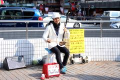 Begåvad japansk gataaktör som busking på trafikljusen royaltyfri foto