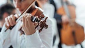 Begåvad violinist som spelar med orkesteren arkivfoto