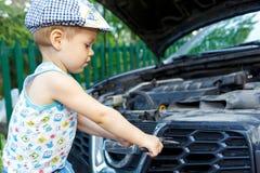 Begaafd jong geitje die motor van een auto herstellen Royalty-vrije Stock Foto