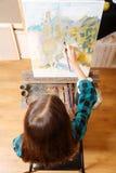 Begaafd meisje die haar talent in de kunststudio aantonen stock foto's