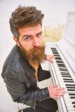 Begaafd musicusconcept De mens in leerjasje zit dichtbij piano muzikaal instrument in wit binnenland op achtergrond Mens stock fotografie