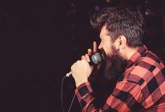 Begaafd vocalistconcept De mens op gespannen gezicht houdt microfoon, het zingen lied, zwarte achtergrond, exemplaarruimte musicu royalty-vrije stock fotografie