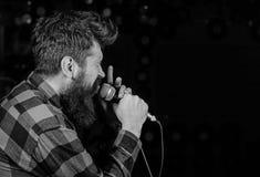 Begaafd vocalistconcept De mens op gespannen gezicht houdt microfoon, het zingen lied, zwarte achtergrond, exemplaarruimte musicu stock fotografie
