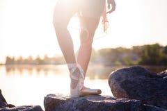 Begaafde ballerina met pointeschoenen op het strand bij zonsondergang stock fotografie