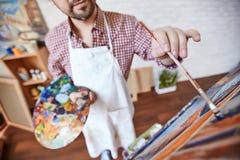 Begaafde Kunstenaar Painting Colorful Picture in Studio stock fotografie