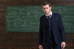 Begaafde wiskundige Klassieke kostuum van de mensen kijkt het formele slijtage slim, bord met vergelijkingenachtergrond Opgelost  stock foto