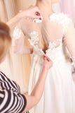 Begabte Damenschneiderin justiert Brautkleid lizenzfreie stockfotos