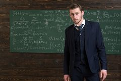 Begabter Mathematiker Klassischer Anzug der Mannformellen kleidung schaut, Tafel mit Gleichungshintergrund intelligent Genie gelö stockfoto