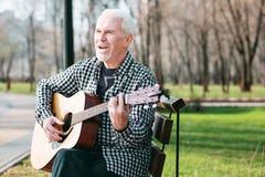 Begabter reifer Mann, der Gitarrenfähigkeiten verbessert lizenzfreies stockbild