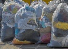 Begagnad kläder i plastpåsar Arkivfoto
