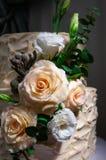 Bege a dois níveis do bolo de casamento Decorado com as rosas feitos a mão do chocolate e as flores artificiais Fotos no interior foto de stock royalty free