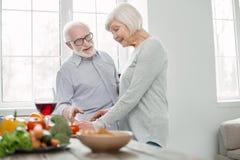 Begeisterte ältere Frau, die Abendessen kocht lizenzfreies stockbild