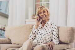 Begeisterte ältere weibliche Person, die pro Telefon spricht lizenzfreie stockfotos
