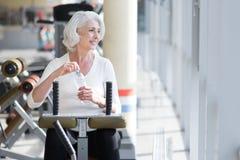 Begeisterte attraktive ältere Frau, die während des Turnhallentrainings sich entspannt stockfotografie