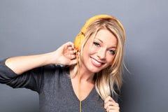 Begeisterte blonde Frau, die Musik auf Kopfhörern hört Stockbild