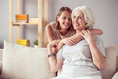Begeisterte erwachsene Frau, die ihre Mutter umfasst Stockfotos