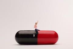 Begeisterte Frau, die auf einer riesigen Pille sitzt Lizenzfreies Stockfoto