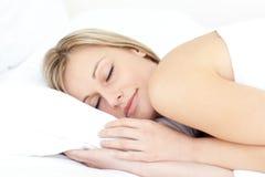 Begeisterte Frau, die auf ihrem Bett schläft Lizenzfreie Stockbilder