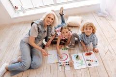Begeisterte frohe Kinder, die auf dem Boden liegen Stockfoto