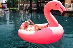 Begeisterte glückliche Frauenschwimmen auf dem Luftflamingo stockbilder