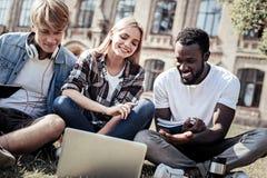 Begeisterte glückliche Studenten, die auf dem Gras sitzen Stockbild