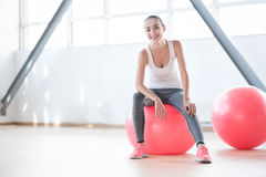 Begeisterte gut gebaut Frau, die auf einem rosa Eignungsball sitzt Stockbild