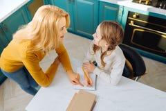 Begeisterte hübsche Mama, die ihre Tochter betrachtet Lizenzfreie Stockfotos