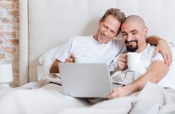 Begeisterte homosexuelle Paare unter Verwendung des Laptops im Schlafzimmer stockfoto