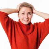 Begeisterte junge blonde Frau, die ihren Kopf für erstaunliche Idee hält Lizenzfreies Stockfoto