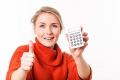 Begeisterte junge blonde Frau mit Taschenrechner und den Daumen oben Lizenzfreies Stockbild