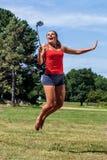 Begeisterte junge Frau, die mit Handy auf Stock springt Stockbild