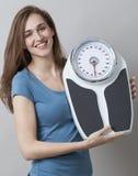Begeisterte junge Frau stolz auf das Anzeigen ihrer Kilos oder der Pfund Verlustes Stockfoto