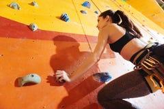 Begeisterte junge Frau, welche oben die Wand in der Turnhalle klettert stockfoto
