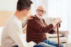 Begeisterte männliche Person, die auf seinen Verwandten hört stockbild