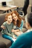 Begeisterte nette Mutter und Tochter, die ihren Doktor betrachtet stockfotografie