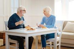 Begeisterte Paare, die Gespräch während des Mittagessens haben Stockfoto
