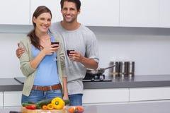 Begeisterte Paare, die ihre Gläser Rotwein klirren Lizenzfreies Stockbild