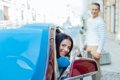 Begeisterte positive Frau, die aus dem Autofenster heraus schaut Stockbilder